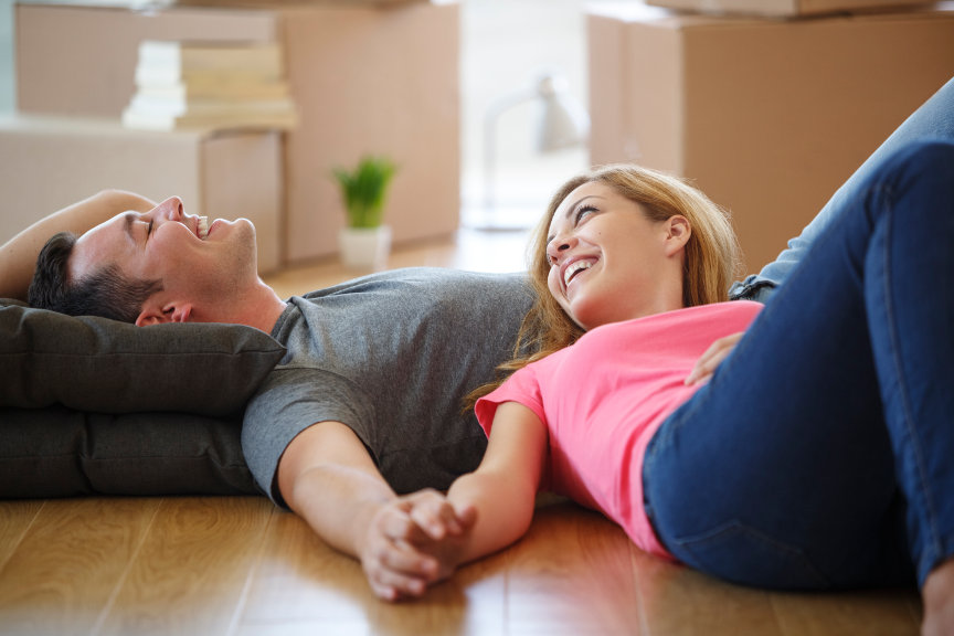 Smiling couple laying on floor with moving boxes in background.